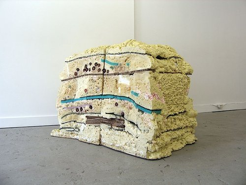 A large sculpture made of two large chunks of foam with various synthetic materials