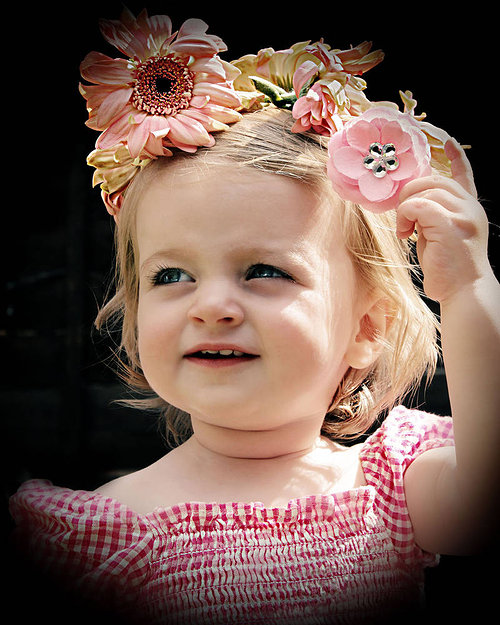 A photograph of a young girl wearing pink with a crown of flowers