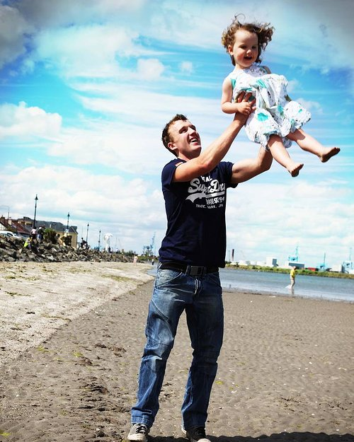 A photograph of a father holding his daughter up