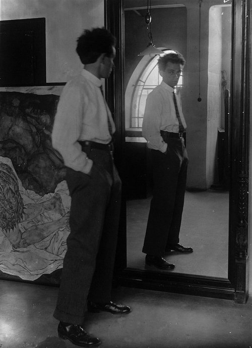 A black and white photo of Egon Schiele standing next to a mirror in his studio