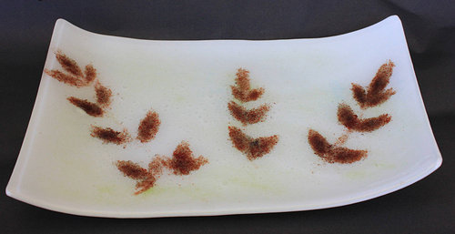 A plate made of two layers of glass with brown leaves between the layers