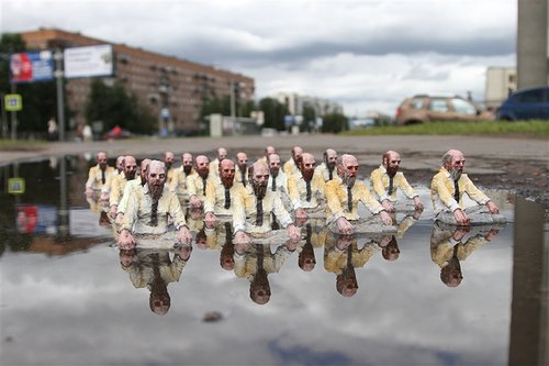 A photo of several sculpted old men wading through a puddle