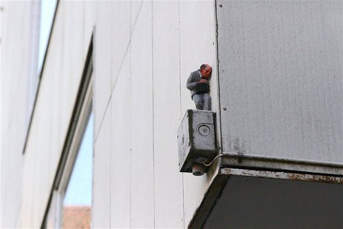 A photo of a tiny sculpted figure sitting atop a power box on the side of a building