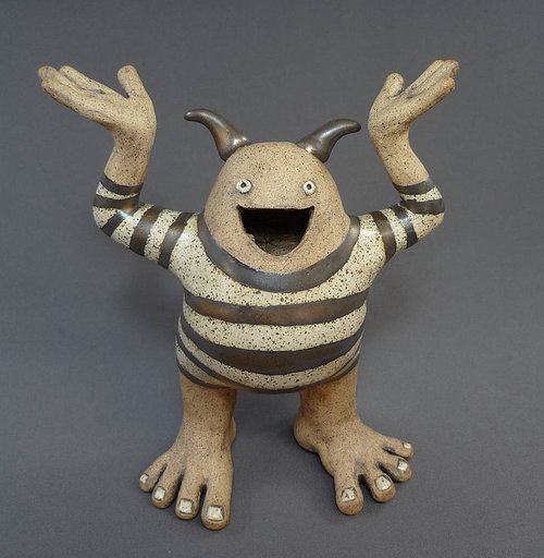 A stoneware sculpture of a happy monster in a striped shirt