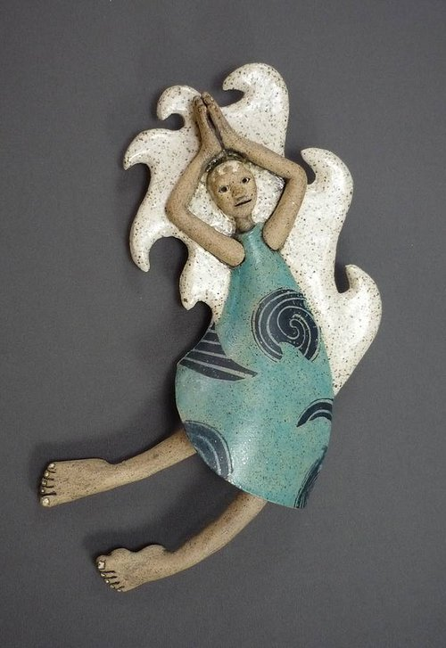 A wall-hanging sculpture of a woman representing the element of water