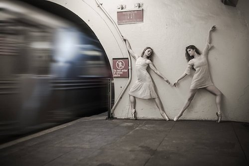 A photograph of two ballerinas performing on an underground train platform