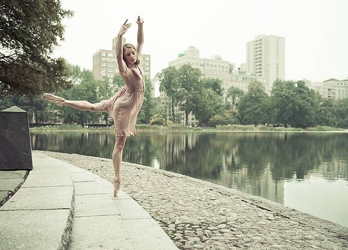 A photo of a ballerina dancing along a seawall in an urban area