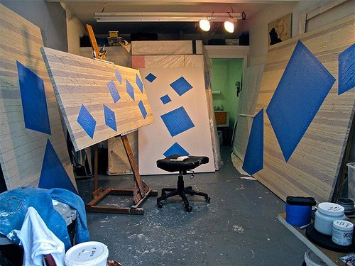 Four paintings with blue squares in a studio