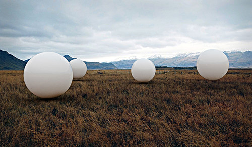A digital image of three white spheres floating over a field