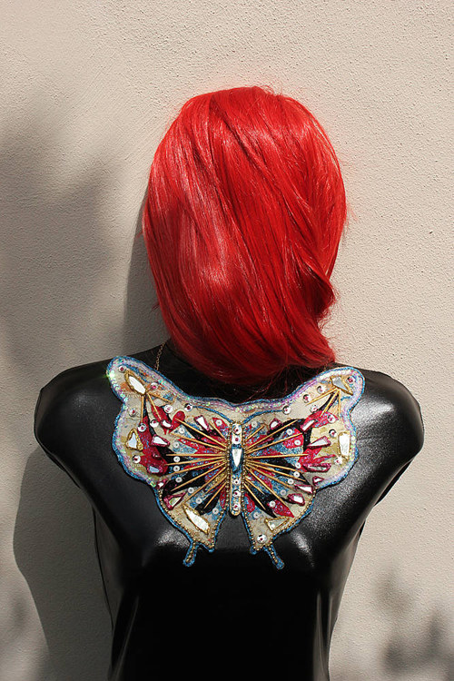 A pectoral fashion accessory made from beads and fabric in the shape of a butterfly