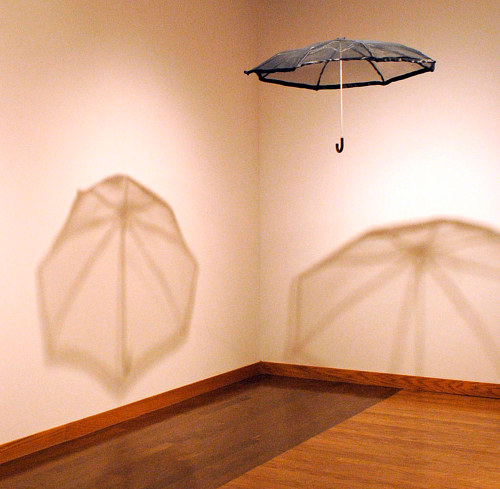 An installation of an umbrella hanging from the ceiling in the corner of a gallery