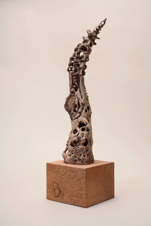 A clay sculpture with many indents and spikes coming upward to a point
