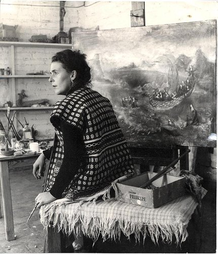 Leonora Carrington sitting in front of her painting aisle