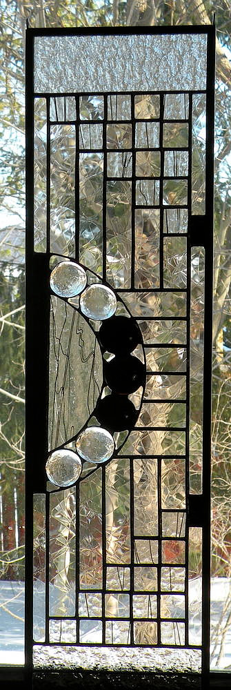 A stained glass panel with squares of black and textured clear glass