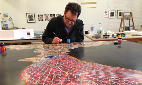 A photo of Fred Tomaselli working on a painting in his studio