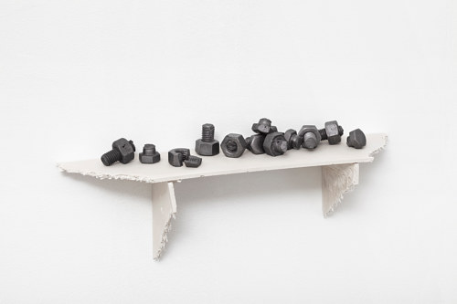 A sculpture with several graphite bolts places on a small shelf