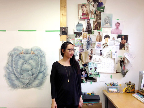 Winnie Truong in her art studio with a large drawing beside her and many sketches on the wall