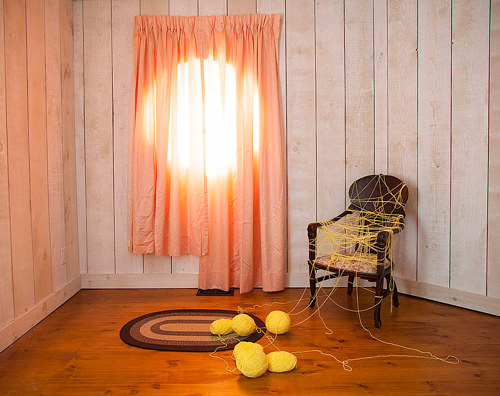 A photograph with a chair, orange drapes, and yellow yarn