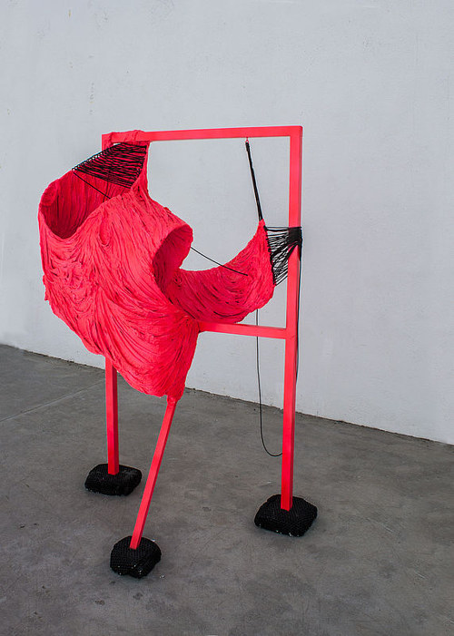 An abstract sculpture composed of synthetic materials and painted neon pink