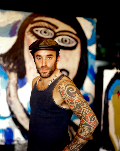 A photograph of artist Ross Brodar in front of a wall mural