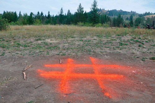 A photo of an outdoor installation with a pound or hashtag symbol spray painted on the ground