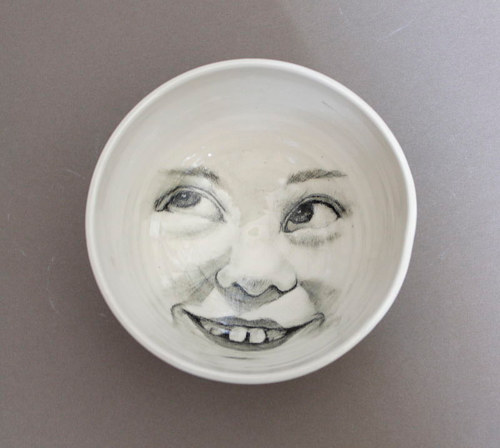 A bowl with a child's face imprinted on the inside in black and white line art