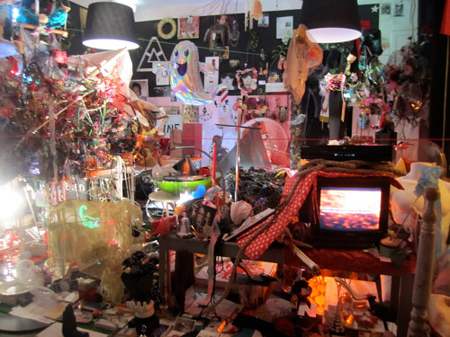 A photo of an installation featuring a space packed with small objects of kitsch