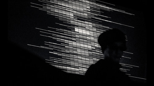 A photo of a shadowed figure standing in front of a black and white data projection