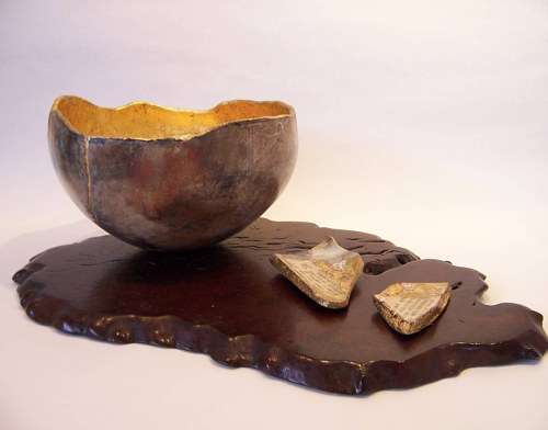 A pit-fired bowl inlaid with gold leaf and Japanese letters