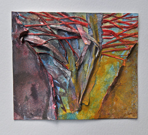 An abstract painting with textural elements of rolled up paper