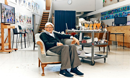 A photo of David Hockney sitting in his home studio in Hollywood