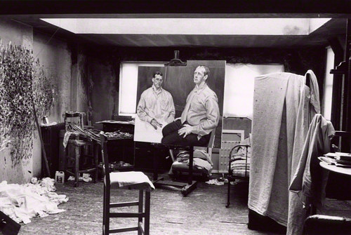 "A black and white photograph of Lucian Freud's studio, with ""Two Brothers from Ulster"" sitting on the easel"