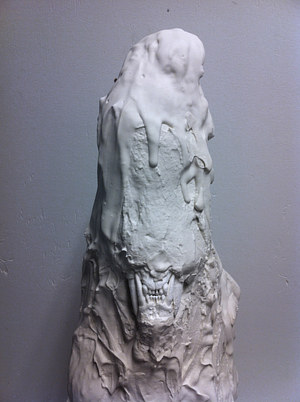 A plaster sculpture constructed to look like a drippy blob with teeth