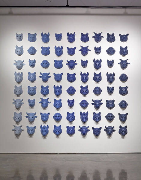 A sculptural installation of a number of blue masks of different types of animals