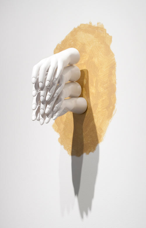 A wall-mounted sculpture using mannequin hands