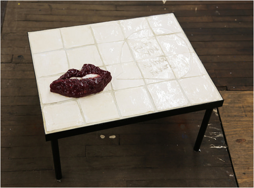 A tiled table with a three-dimensional pair of lips functioning as an ashtray