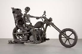 A bronze sculpture of a skeleton riding a motorcycle