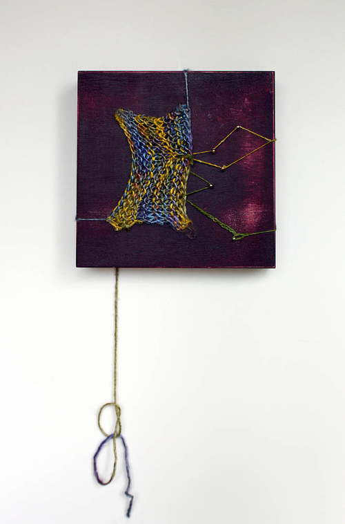 A mixed media work on wood panel with a strand  of yarn trailing below it