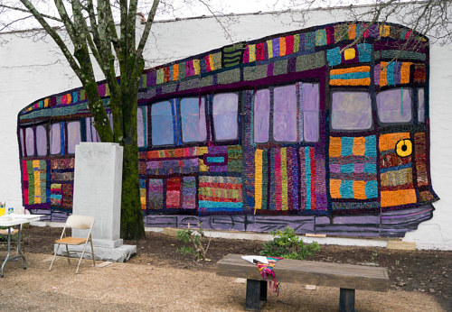 An outdoor yarn mural of a colourful trolley
