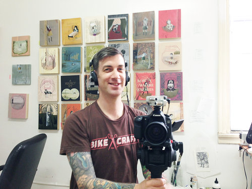 Chris with camera and paintings in the background