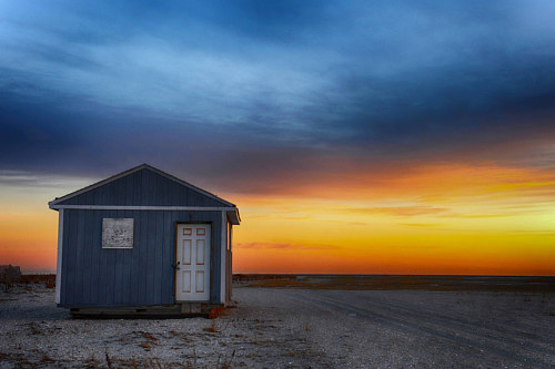 A photo of a small shack on a beach at sunset