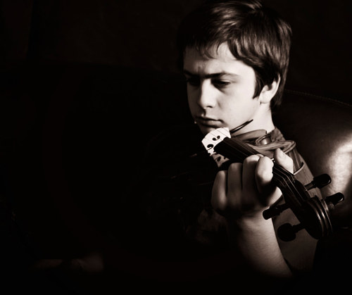 A black and white photograph of a young man playing violin