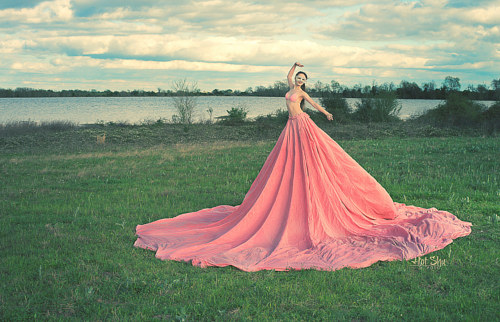 A photo of a woman in a very long pink dress near the water