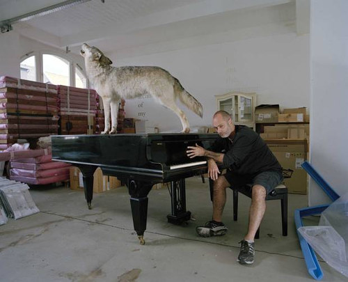 A photo of Douglas Gordon sitting at a piano in his studio