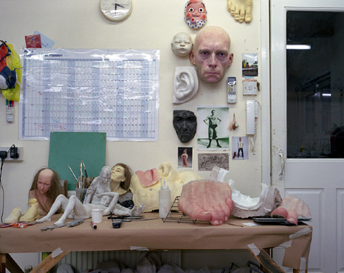 A photo of a table full of sculpted body parts in Ron Mueck's studio
