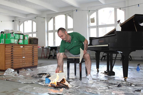 A photo of Douglas Gordon burning piano music in his studio