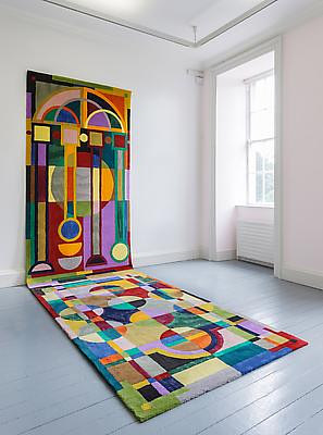 A brightly coloured hand-tufted rug leaning against the wall of a gallery