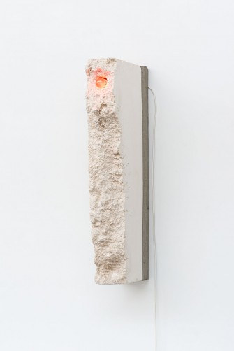 A piece of foam encasing an electric lamp hanging on the wall of a gallery