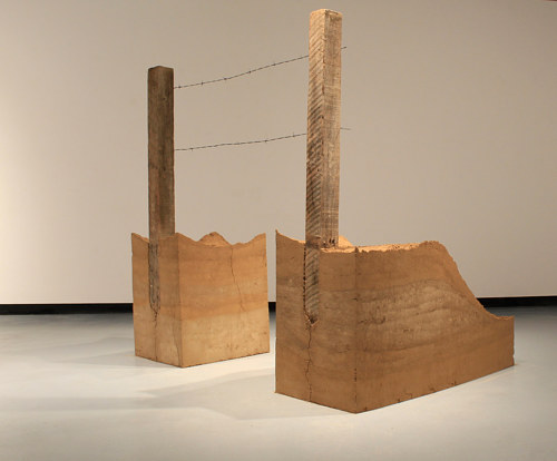 A sculpture consisting of two wood blocks with a single link of wire fencing between them