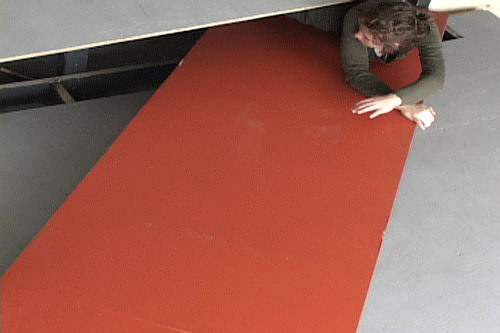 A performance still of a person laying flat on a long red sheet of wood